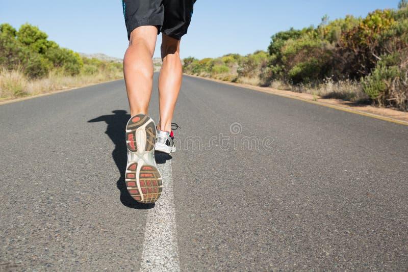 Подходящий человек jogging на открытой дороге стоковые фотографии rf