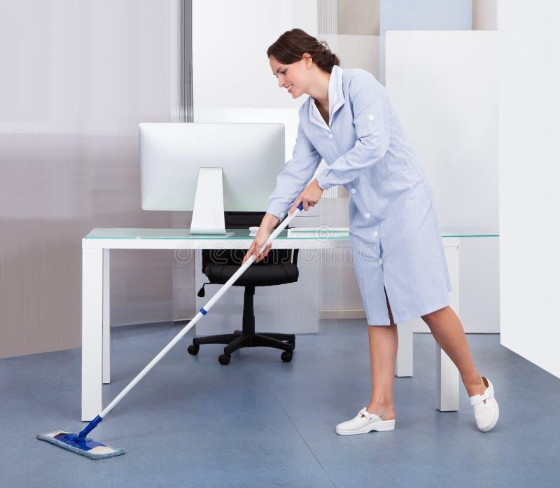Пол чистки горничной в офисе стоковое изображение