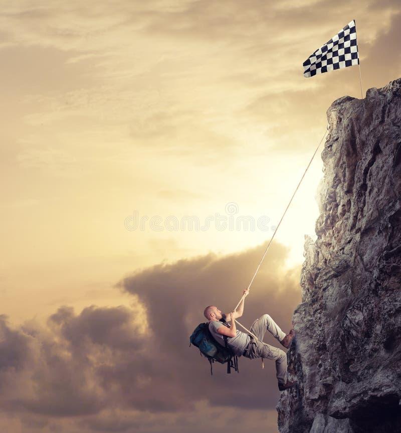 Подъем бизнесмена гора для того чтобы получить флаг Цель бизнеса достижения и трудная концепция карьеры стоковое фото