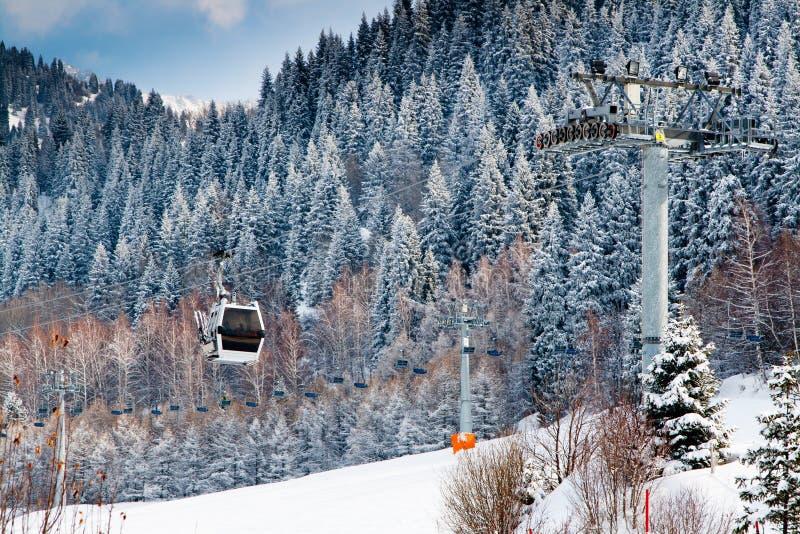 Подъем и снег лыжи предусматривали горы с предпосылкой сосен на курорте Ak Bulak, Казахстане стоковые изображения rf