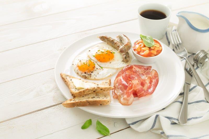 Польностью английский завтрак на белых плите и деревянном столе стоковые фотографии rf