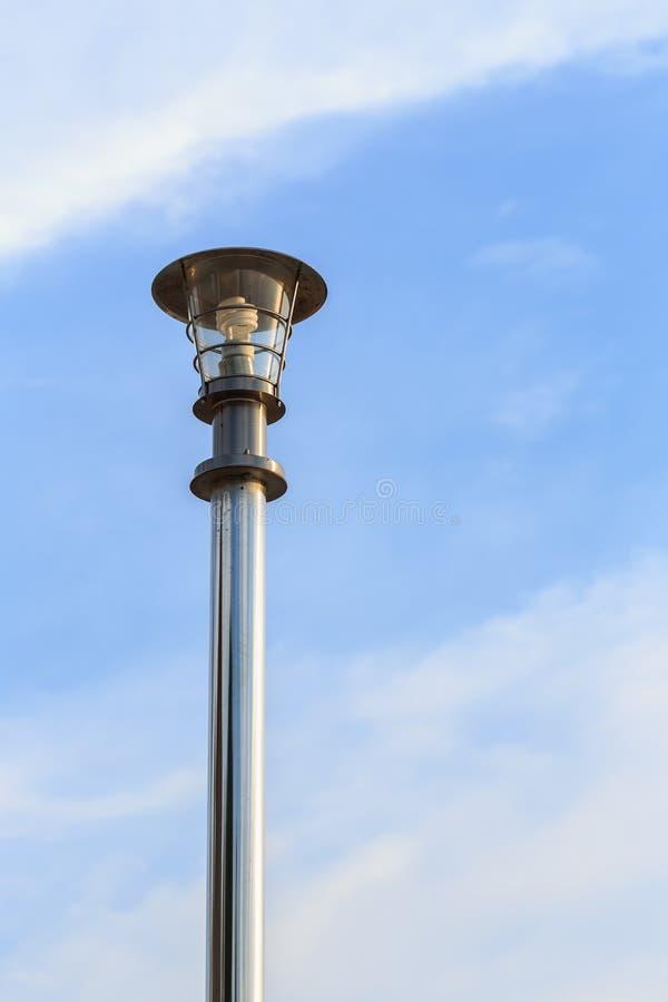 Поляк лампы нержавеющей стали на дороге на голубом небе стоковая фотография