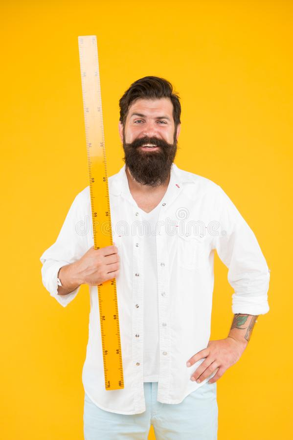 Правитель удерживания хипстера человека бородатый Длина измерения Определять размер высокорослое и длину Большой размер Измерение стоковое изображение rf