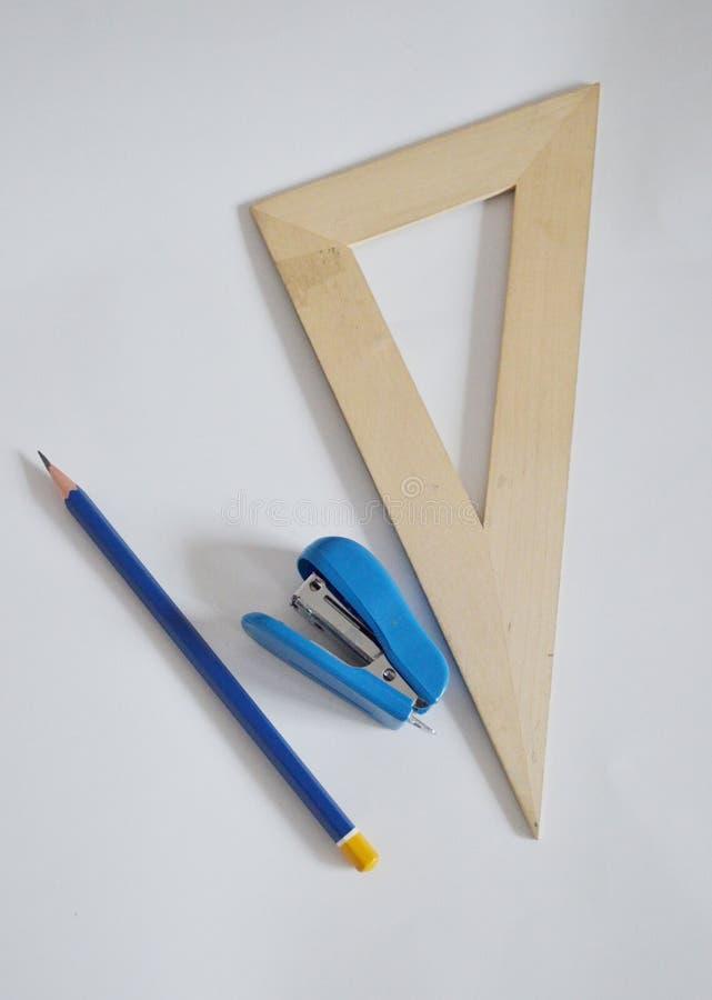 Правитель, сшиватель, карандаш на белой предпосылке Фото стоковое изображение