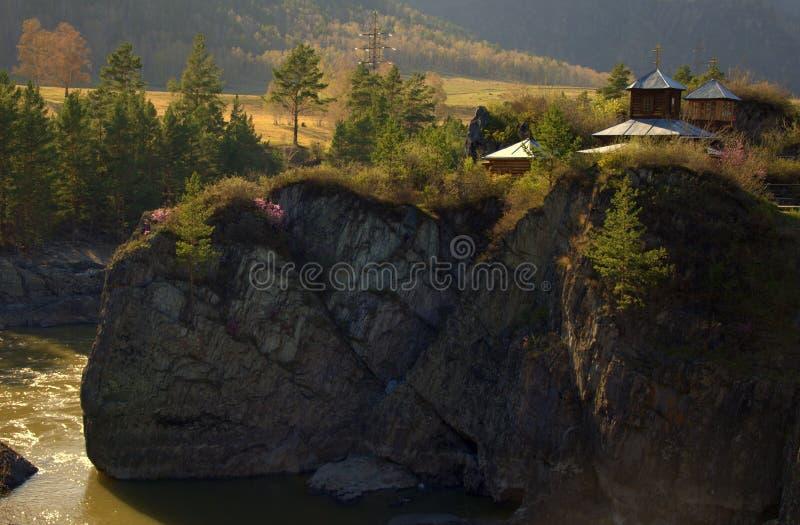 Правоверная часовня на краях высокой скалы и стремительного реки горы пропуская на ноге Altai, Сибирь, Россия стоковая фотография rf