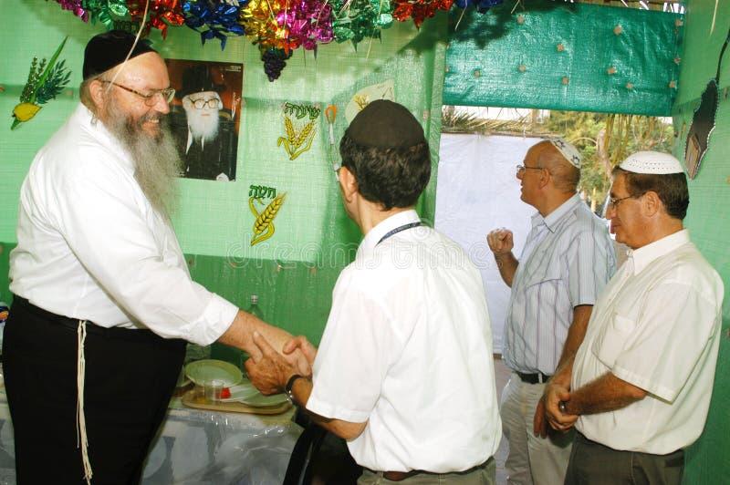 Правоверные еврейства празднуют Sukkot в Sukkah стоковое фото