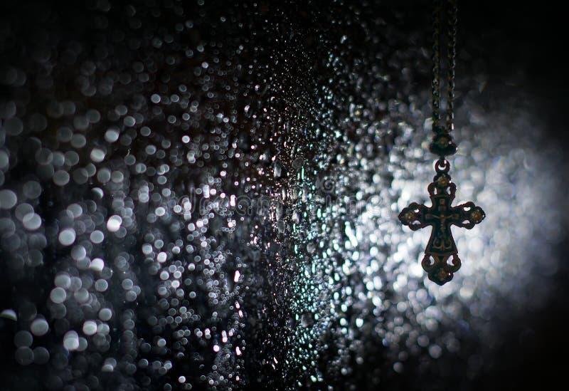 Правоверный и католический крест реликвии со святым распятием на предпосылке влажного стекла вечером в свете контура стоковые изображения rf