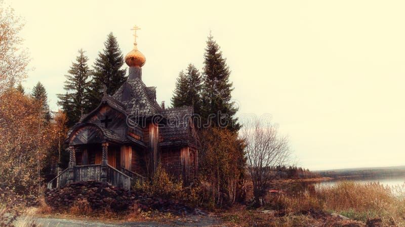 Православная церков церковь стоит в лесе на береге озера стоковое фото