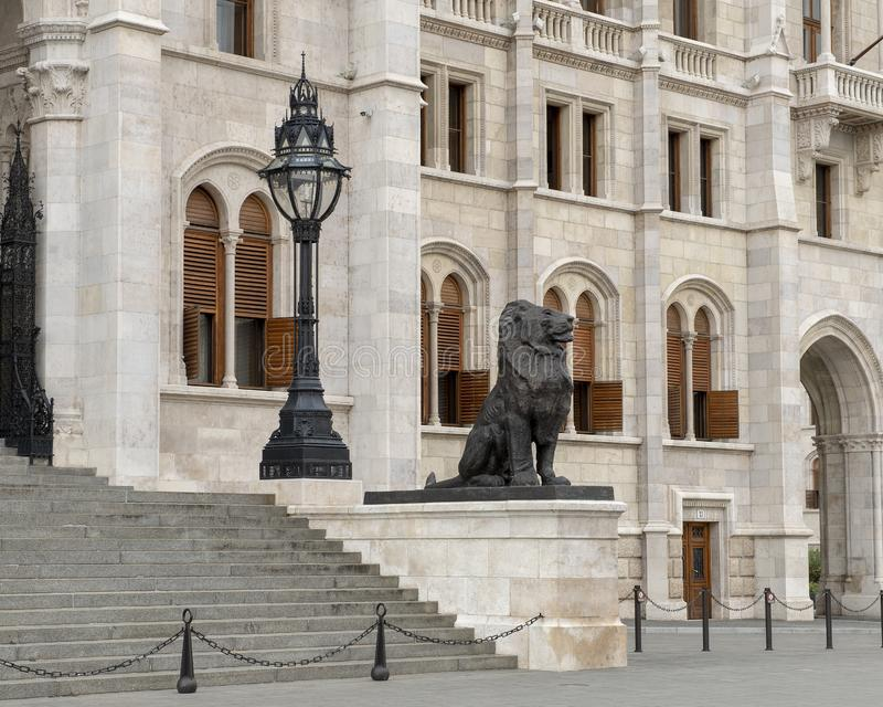 Право 2 бронзовых статуй льва фланкируя восточный вход венгерского здания парламента, Будапешта стоковое фото rf
