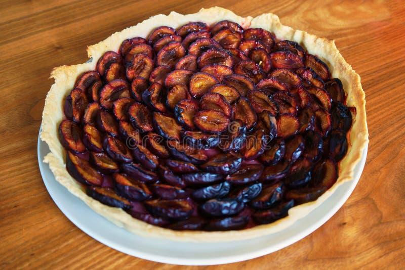 Право пирога сливы вне печь на a с плитой на деревянном столе стоковое изображение rf