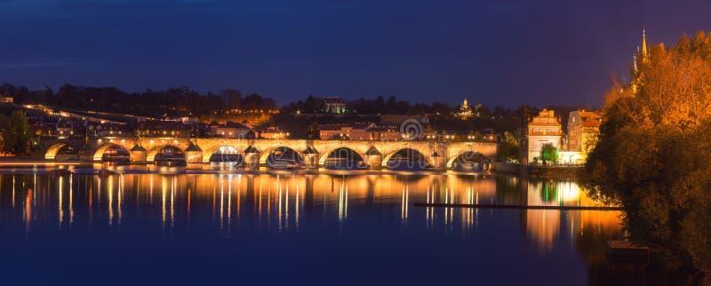 Прага, взгляд загоренного Карлова моста Karluv больше всего с отражением в воде, городским пейзажем ночи сценарным, чехией стоковые изображения rf