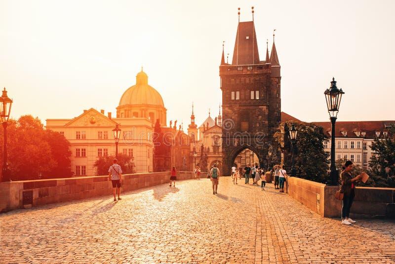 Прага, восход солнца над Карловым мостом с туристом идя до конца стоковое фото