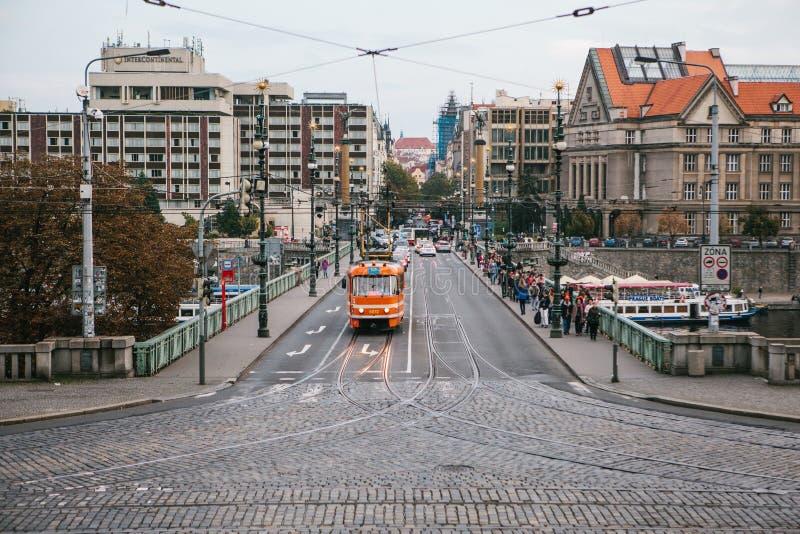 Прага, 24-ое сентября 2017: Трамвай и много автомобили следовать им на мосте Близрасположенная прогулка людей на пешеходной сторо стоковая фотография rf