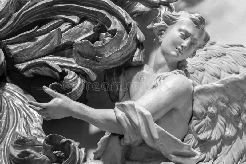 ПРАГА, ЧЕХИЯ, 2018: Высекаенная polychrome барочная статуя ангела от бортового алтара в Св.е Франциск Св. Франциск Assisi стоковые изображения