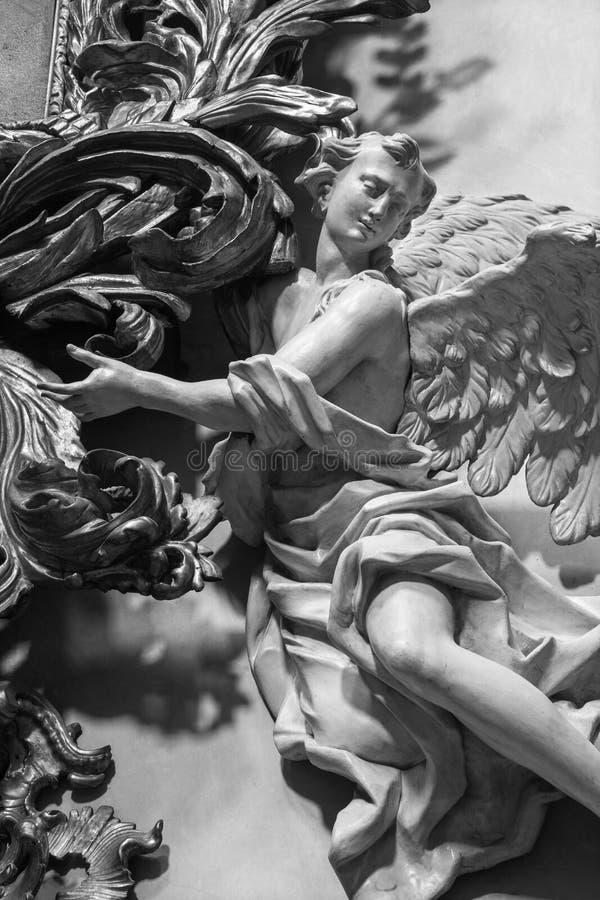 ПРАГА, ЧЕХИЯ, 2018: Высекаенная polychrome барочная статуя ангела от бортового алтара в Св.е Франциск Св. Франциск церков Assisi стоковые фотографии rf