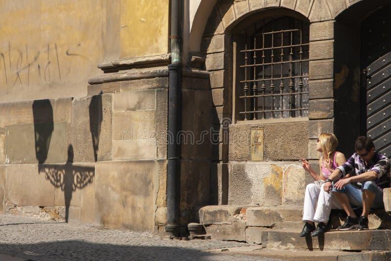 Прага, чехия - 19-ое апреля 2011: Женщина и человек сидя на серой каменной лестнице стоковые фото