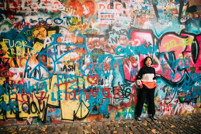 Прага, Чешская Республика Китайский турист женщины представляя для фото около известной стену Джон Леннон Стена заполнена с стоковое изображение