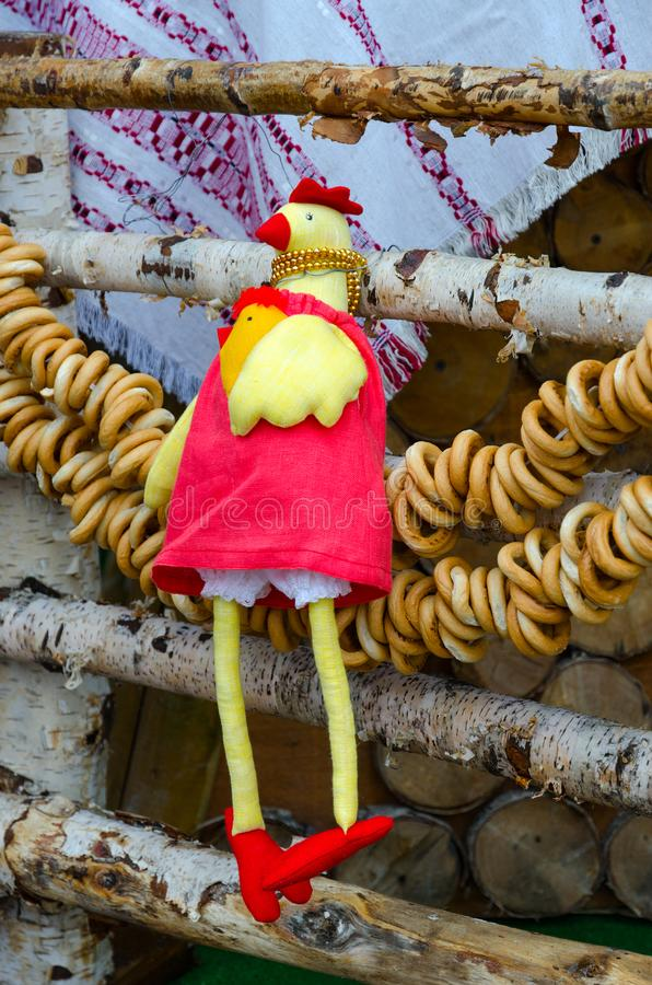 Праздненства Shrovetide Оформление торговых мест Игрушк-петух и пачка бейгл, вися на загородке березы стоковое фото rf