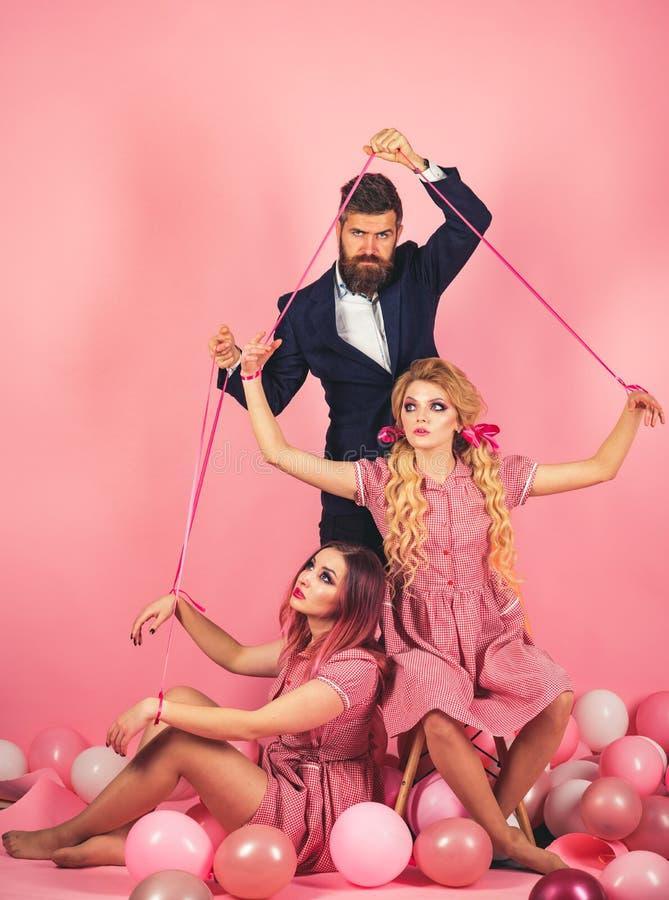 праздники и куклы засилье и зависимость творческая идея Любовный треугольник ретро девушки и мастер в воздушных шарах партии стоковые изображения