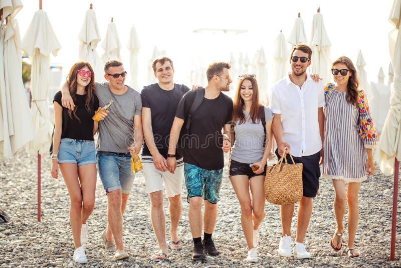 праздники, каникулы группа в составе друзья имея потеху на пляже, идти, пиве питья, усмехаться и обнимать стоковая фотография