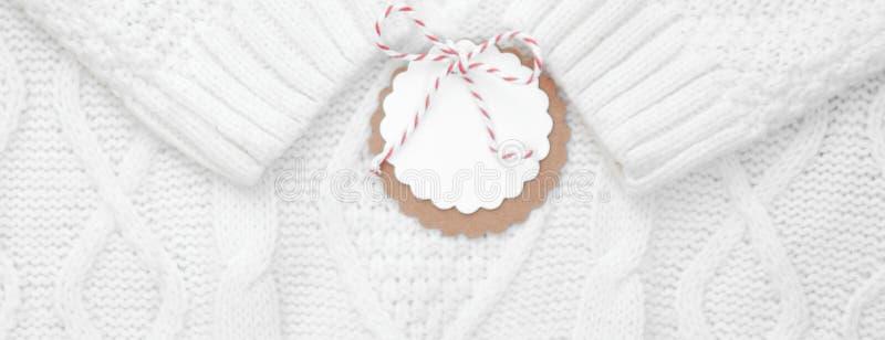 Праздничная белизна связала свитер зимы с ярлыком для поздравлений зима снежка положения праздников мальчика знамена стоковое изображение
