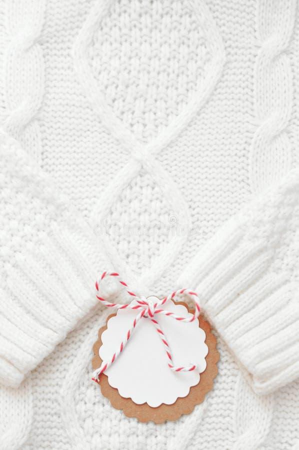 Праздничная белизна связала свитер зимы с ярлыком для поздравлений зима снежка положения праздников мальчика vertikal стоковое изображение rf
