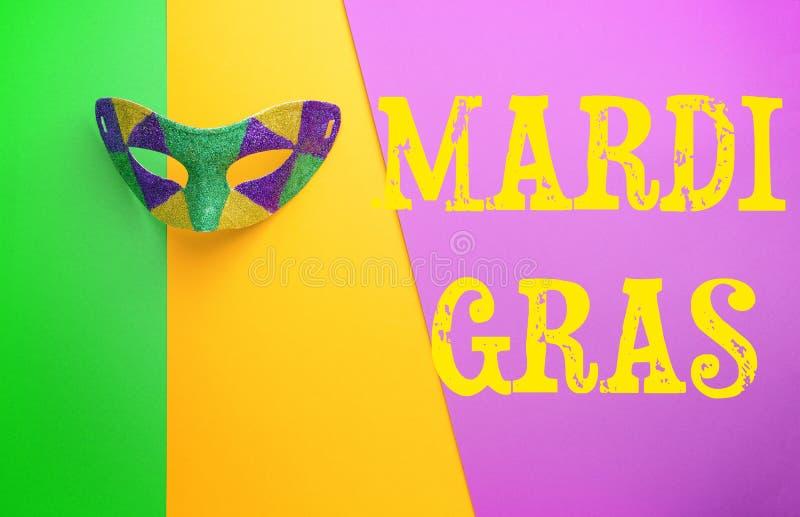 Праздничная маска с МАРДИ ГРА текста (также известным как жирный вторник) на предпосылке цвета стоковая фотография rf