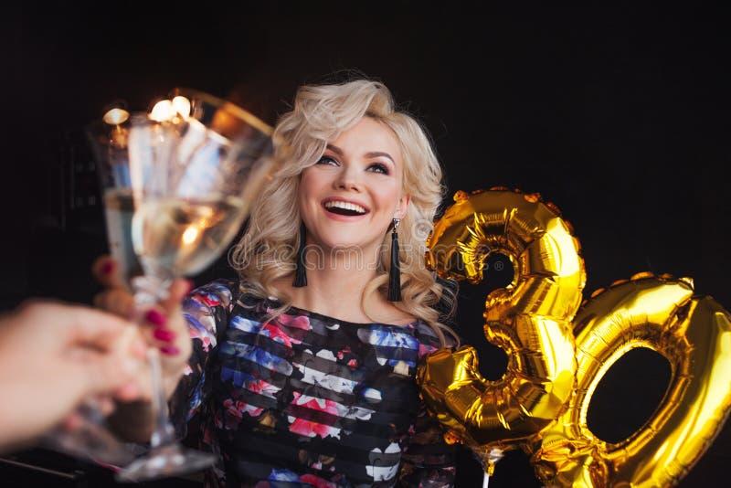 Праздничная партия, молодая красивая блондинка поднимает тост стоковая фотография
