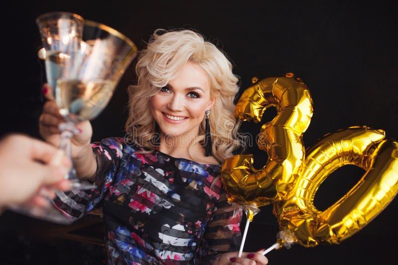 Праздничная партия, шампанское молодой красивой блондинкы выпивая и clinking стекла стоковое изображение rf