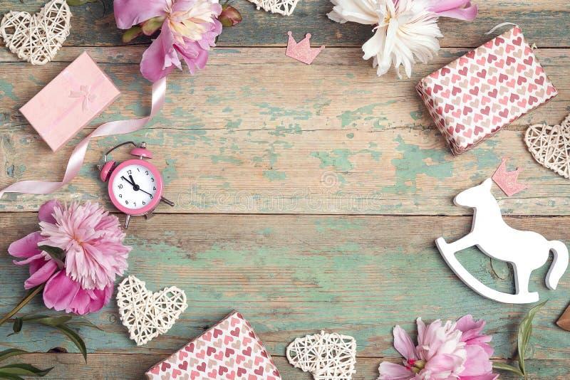 Праздничная рамка розовых пионов, подарков и сердец на старой предпосылке бирюзы с затрапезной краской Концепция дня рождения мал стоковое изображение rf
