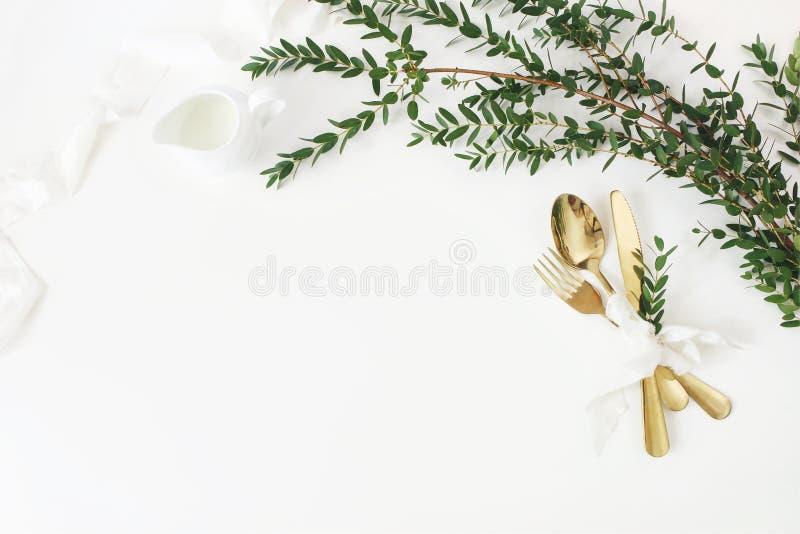 Праздничная свадьба, сервировка стола дня рождения с золотым столовым прибором, parvifolia эвкалипта, лента шелка и кувшин молока стоковые фото