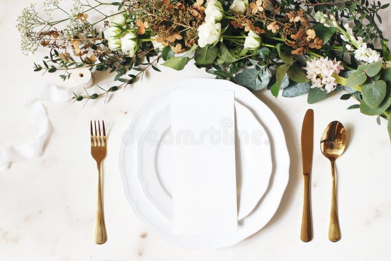 Праздничная свадьба, сервировка стола дня рождения с золотым столовым прибором, лента шелка, ветви эвкалипта, гортензия и белые р стоковое фото rf