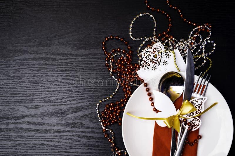 Праздничная сервировка стола для обедающего рождества или Нового Года: винтажная вилка, ложка, нож на красной салфетке и украшени стоковые изображения