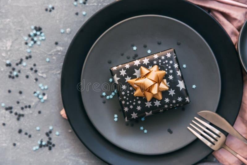 Праздничная сервировка стола партии с плитой, вилкой, ножом, и подарочной коробкой стоковая фотография