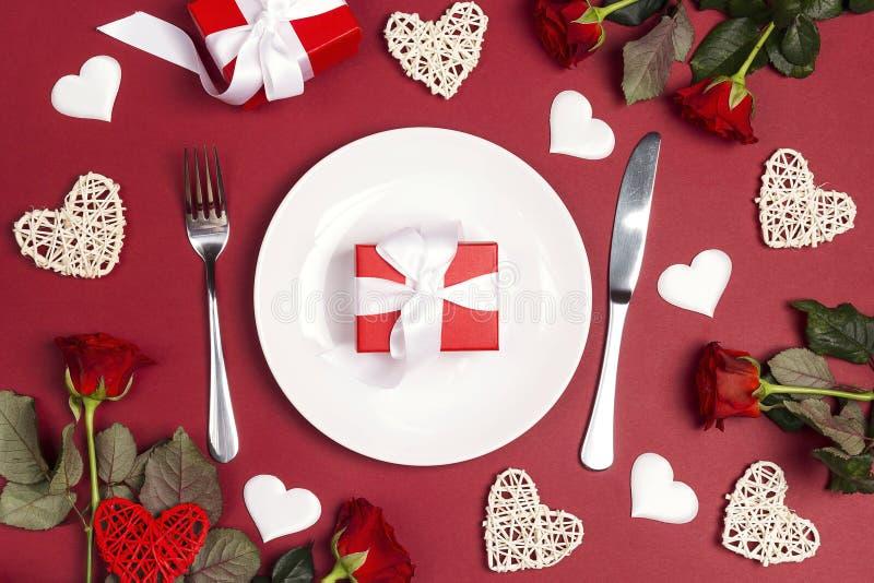 Праздничная сервировка стола со столовым прибором, подняла цветки и подарочные коробки на красной таблице valentines st сердца дн стоковое фото