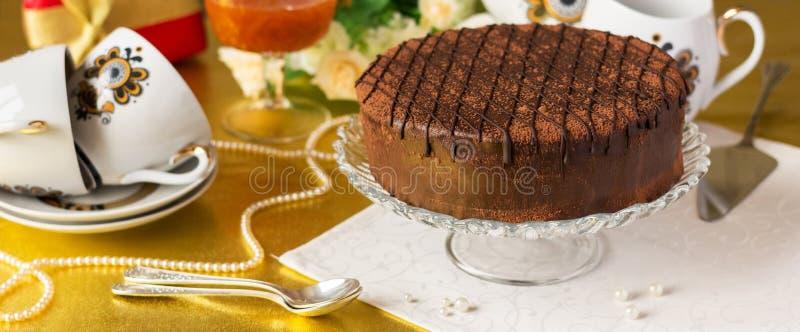 Праздничная сервировка таблицы чая, шоколадный торт в вазе на салфетке стоковое изображение rf