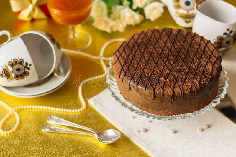 Праздничная таблица с шоколадным тортом на плите, комплекте чая, ложках стоковое фото rf