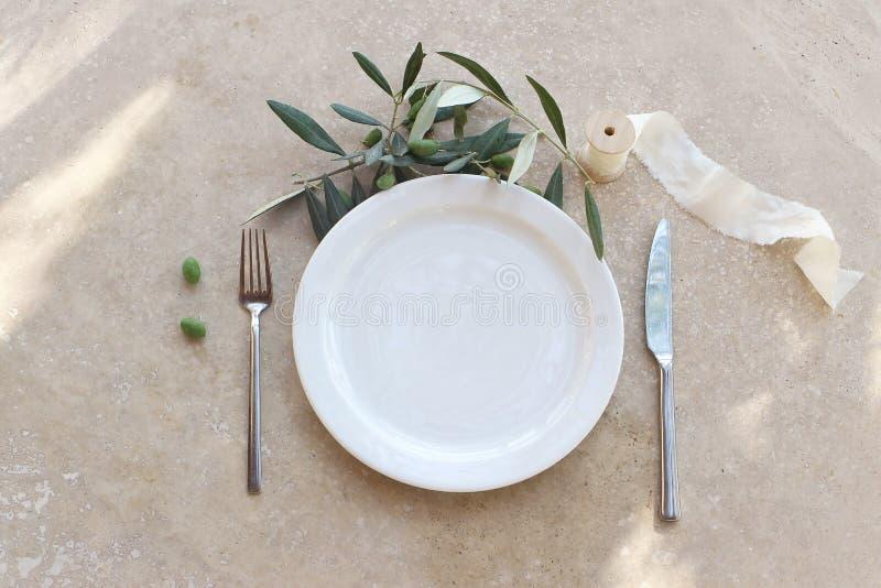 Праздничная установка лета таблицы с серебряными столовым прибором, оливковой веткой, плитой фарфора и лентой шелка На мраморной  стоковые изображения rf