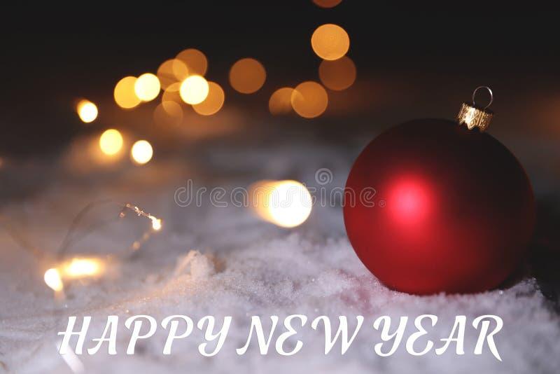 Праздничное украшение на снеге и сообщение С НОВЫМ ГОДОМ! против темной предпосылки стоковое изображение