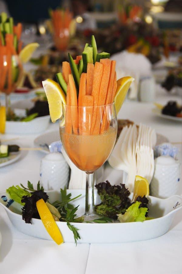 Праздничное украшение таблицы в форме огурца и моркови с лимоном в стеклянном кубке стоковая фотография rf