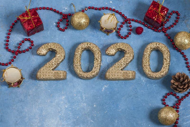 Празднично-голубой фон с красными рождественскими украшениями и золотыми номерами 2020 года Новый год и Рождество стоковая фотография