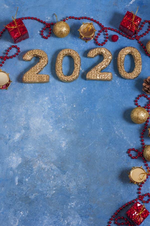 Празднично-голубой фон с красными рождественскими украшениями и золотыми номерами 2020 года Новый год и Рождество стоковые фотографии rf