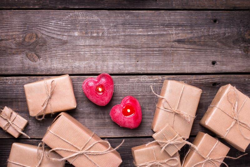 Праздничные подарочные коробки с настоящими моментами и 2 горящими свечами в fo стоковая фотография rf
