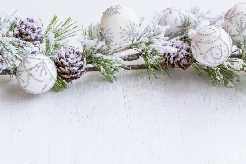 Праздничные снежные украшения ветви сосны с конусами и серебром и стоковое изображение rf