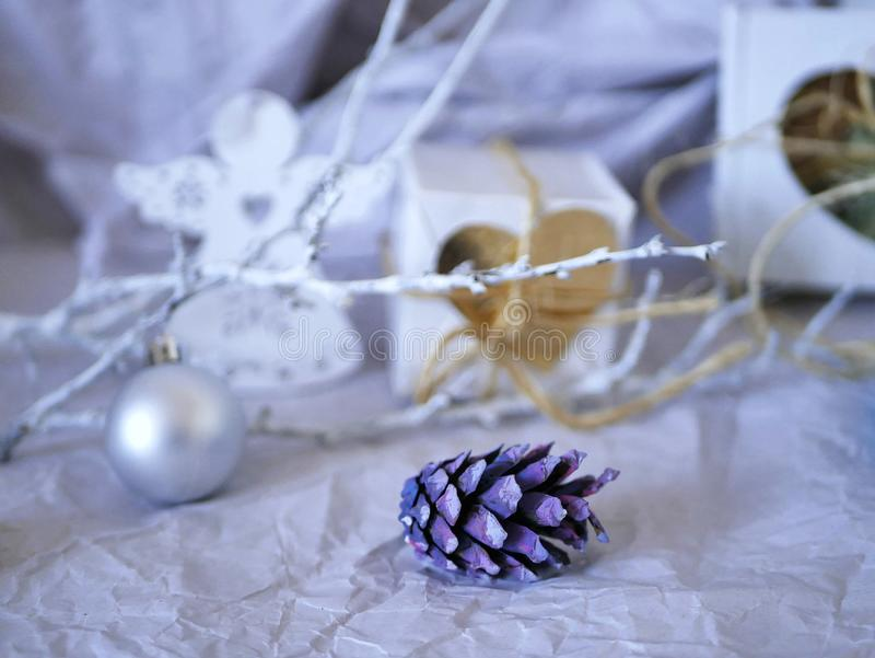 Праздничные украшения рождества пурпурных конусов, белых ветвей, серебряного шарика, подарков на светлой предпосылке стоковые фотографии rf