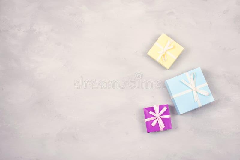 Праздничный, день рождения, предпосылка подарка пастельная минимальная Пестротканые подарочные коробки на серой предпосылке цемен стоковая фотография