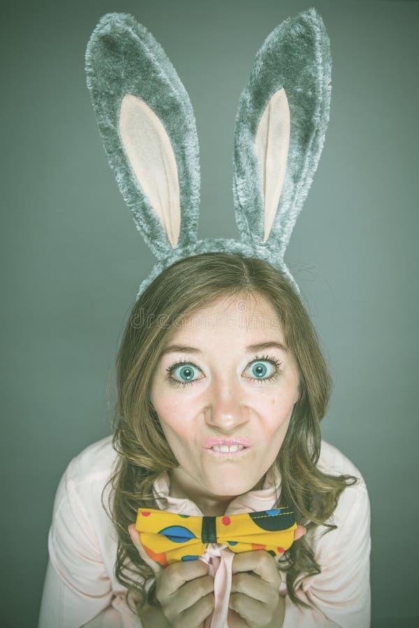 Праздничный сезон зайчика и яичек счастливая современная женщина в ушах зайчика пасхи изолированных на серой предпосылке стоковое фото rf