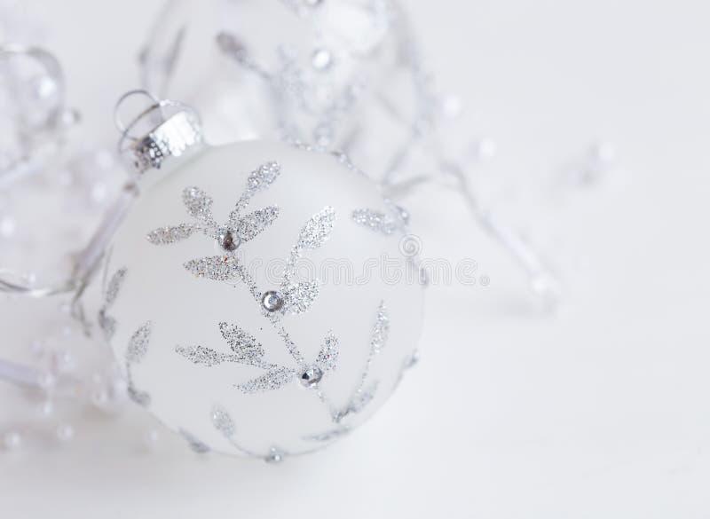 Праздничный серебряный стеклянный шарик с орнаментом яркого блеска, рождественской елкой d стоковое фото