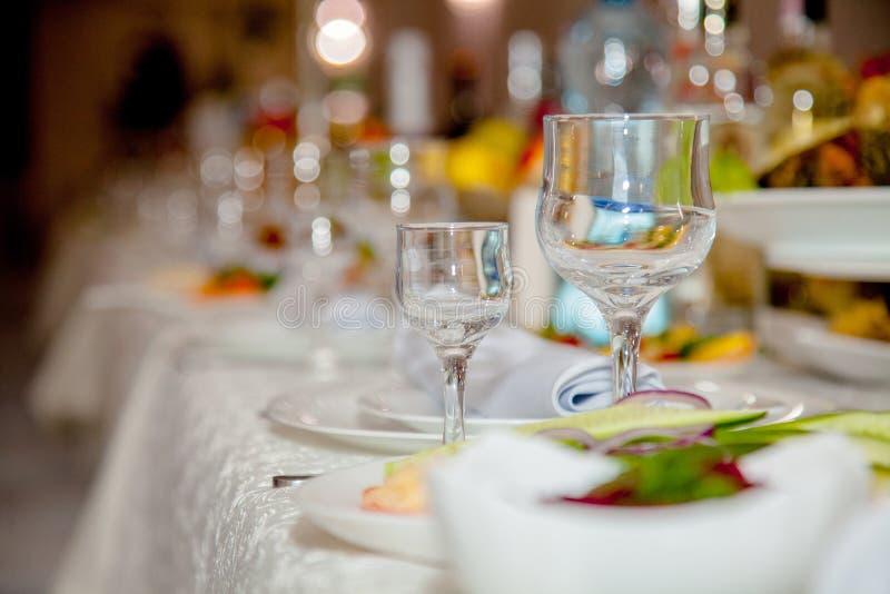 Праздничный tableware со стеклами на таблице Пустые стекла стоят около плит и вилок на таблице банкета украшенной с белизной стоковая фотография
