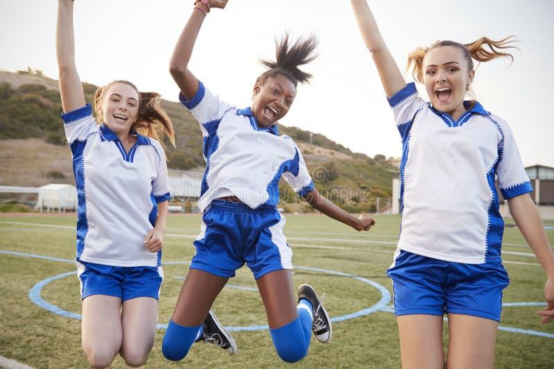 Праздновать женских студентов средней школы играя в футбольной команде стоковое изображение rf